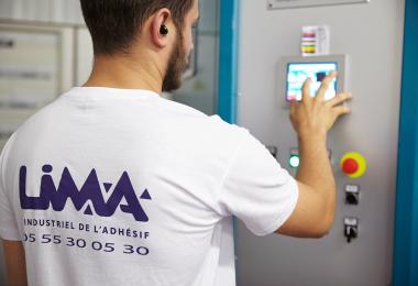 membre de l'équipe de professionnel de chez LIMA Adhésifs en train de régler une machine